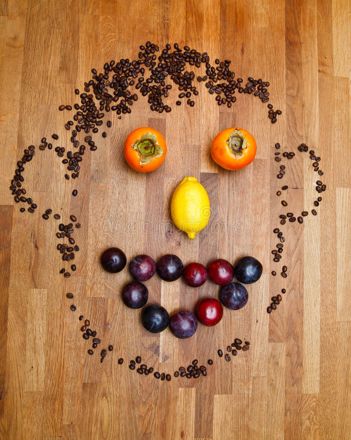 Face made of fruits. On wooden background royalty free stock photography