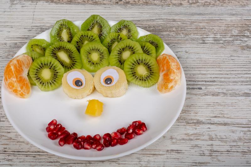 A face made of fruits on the plate. royalty free stock photo