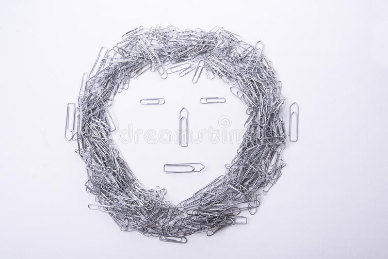 Face make from paper clips on white. Background royalty free stock images