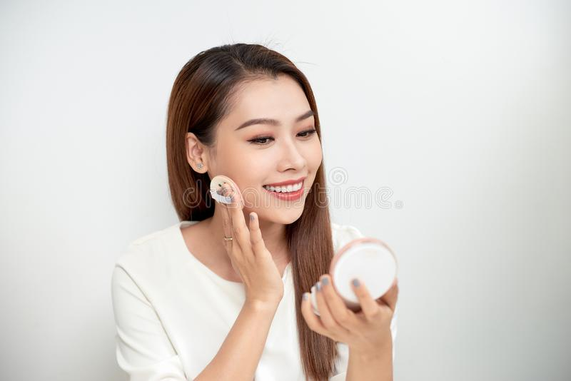 Face Make-Up. Closeup Of Female Applying Dry Powder Foundation Looking In Mirror. Portrait Of Young Woman Putting Makeup royalty free stock photo