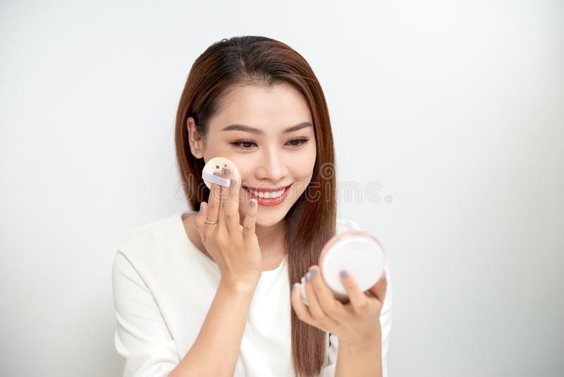 Face Make-Up. Closeup Of Female Applying Dry Powder Foundat. Ion Looking In Mirror. Portrait Of Young Woman Putting Makeup Powder With Cosmetic Cushion On Her royalty free stock images