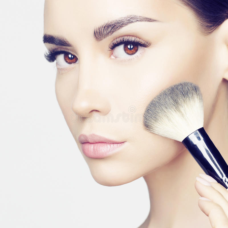 Face Makeup. Studio fashion photo of beautiful young lady applying blush. Beauty and care. Extension eyelashes. Spa salon. Perfect face makeup stock image