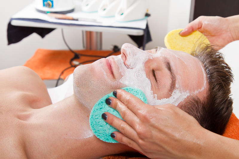 Face mask. Therapist applying a face mask to a beautiful young man in a spa using a cosmetics brush stock photography