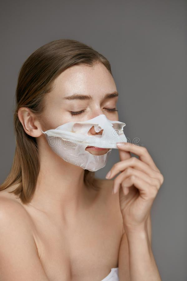 Face mask. Woman taking off white sheet mask from facial skin royalty free stock images