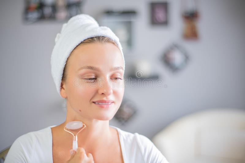 Face massage. Beautiful woman is getting massage face using jade facial roller for skin care. Beauty treatment at home royalty free stock image