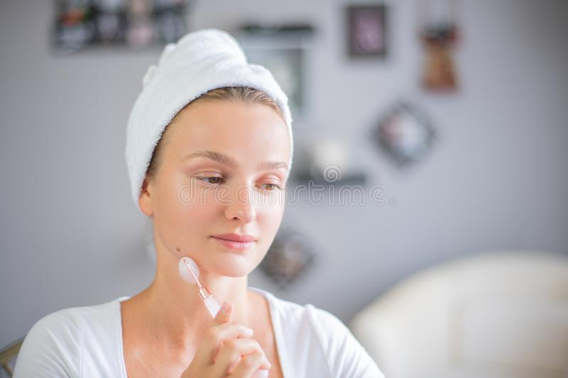 Face massage. Beautiful woman is getting massage face using jade facial roller for skin care. Beauty treatment at home royalty free stock photo