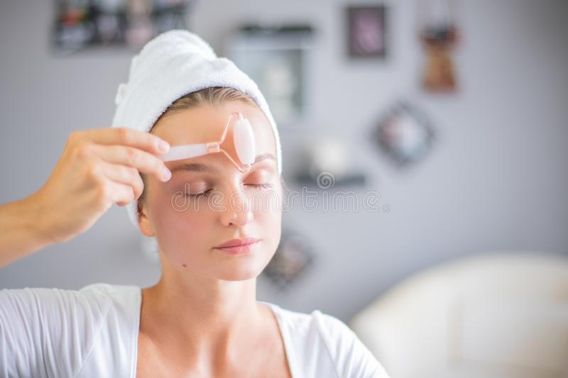 Face massage. Beautiful woman is getting massage face using jade facial roller for skin care. Beauty treatment at home stock photography