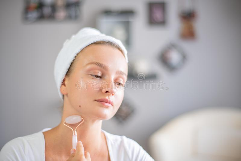 Face massage. Beautiful woman is getting massage face using jade facial roller for skin care. Beauty treatment at home royalty free stock photos