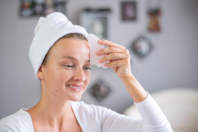Face massage. Beautiful woman is getting massage face using jade stone for skin care. Beauty treatment at home royalty free stock photos