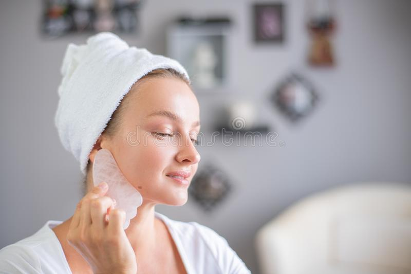 Face massage. Beautiful woman is getting massage face using jade stone for skin care. Beauty treatment at home royalty free stock images