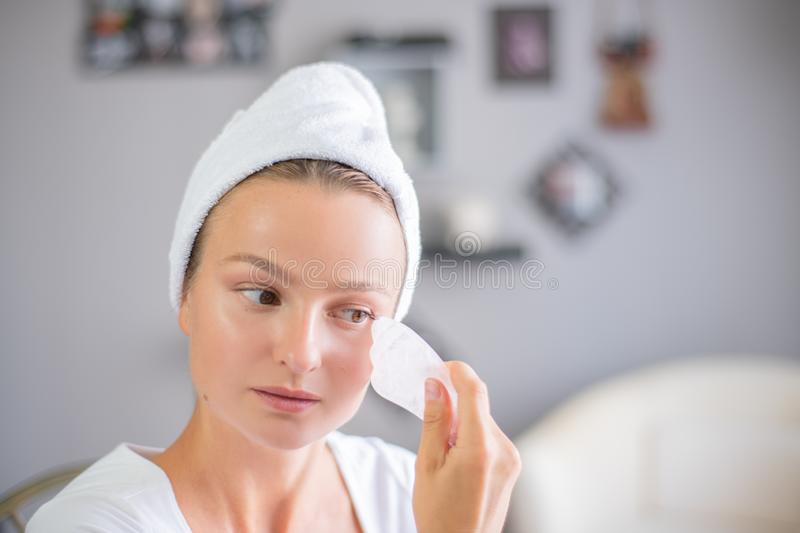 Face massage. Beautiful woman is getting massage face using jade stone for skin care. Beauty treatment at home royalty free stock image
