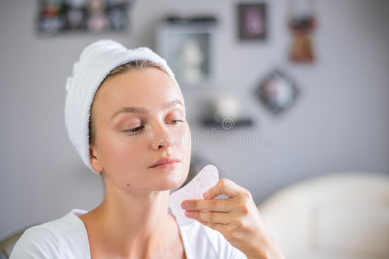 Face massage. Beautiful woman is getting massage face using jade stone for skin care. Beauty treatment at home royalty free stock photo