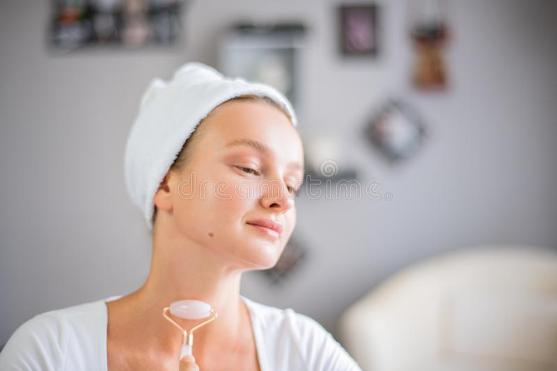 Face massage. Beautiful woman is getting massage face using jade facial roller for skin care. Beauty treatment at home royalty free stock photography