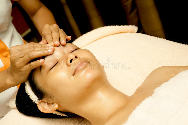 Face Massage at Beauty Clinic. Ethnic young woman having face massage at beauty clinic stock image