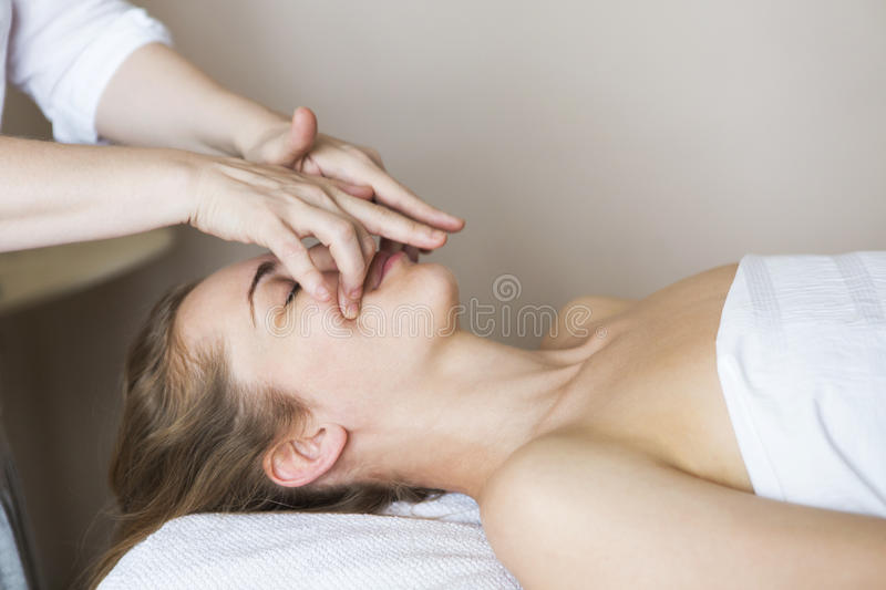 Face massage or beauty treatment in spa salon. Young pretty women face massage or beauty treatment in spa salon stock image