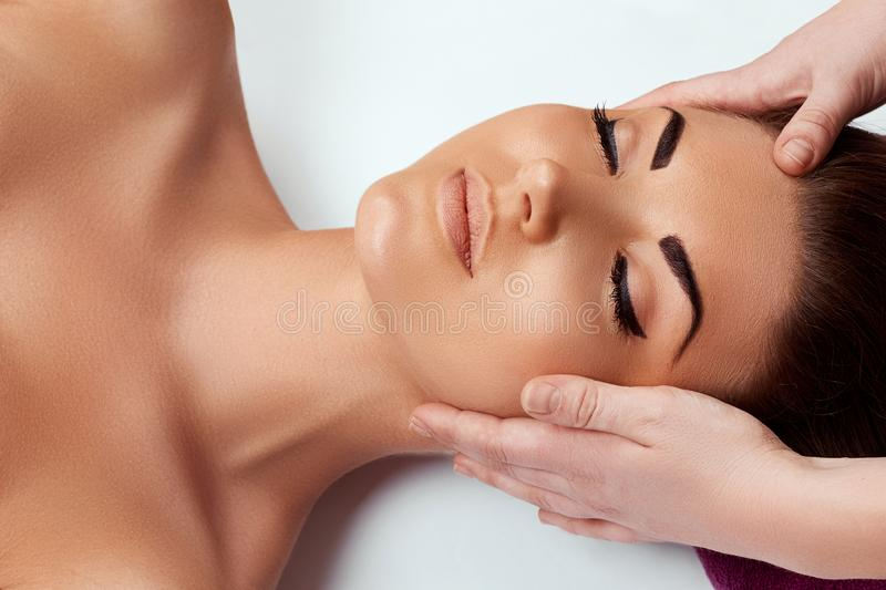 Face massage. Close-up of young woman getting spa massage treatment at beauty spa salon.Spa skin and body care. stock photos