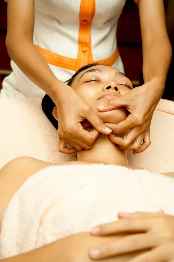 Face Massage at Facial Treatment. Asian young woman face massage in facial treatment royalty free stock photography