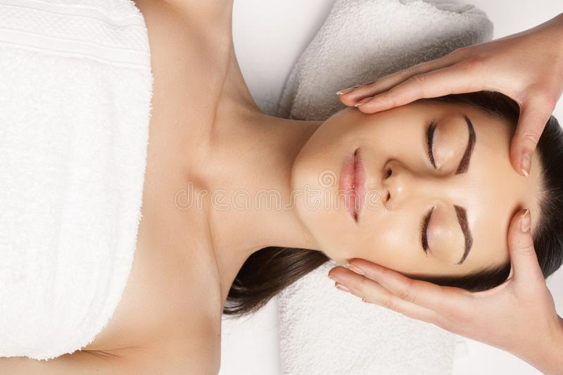 Face massage. people, beauty, spa, healthy lifestyle and relaxation concept - close up of beautiful young woman lying with closed royalty free stock images