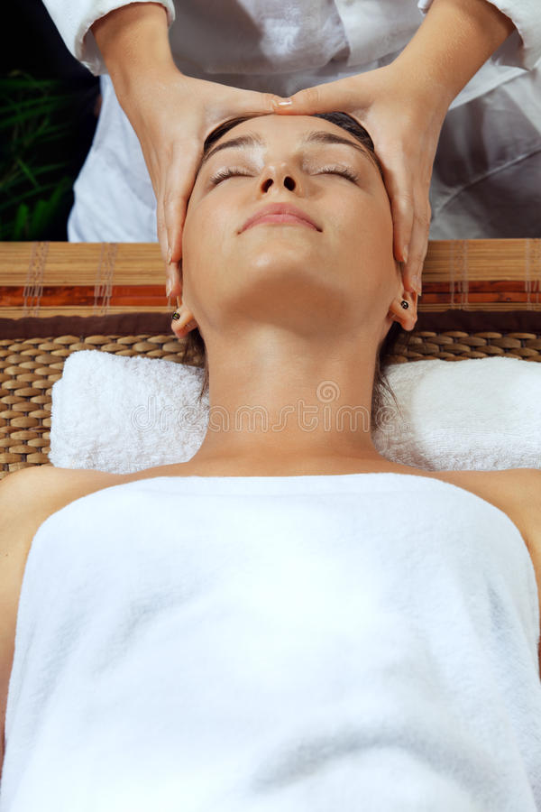 Face massage. Portrait of young beautiful woman in spa environment stock photos