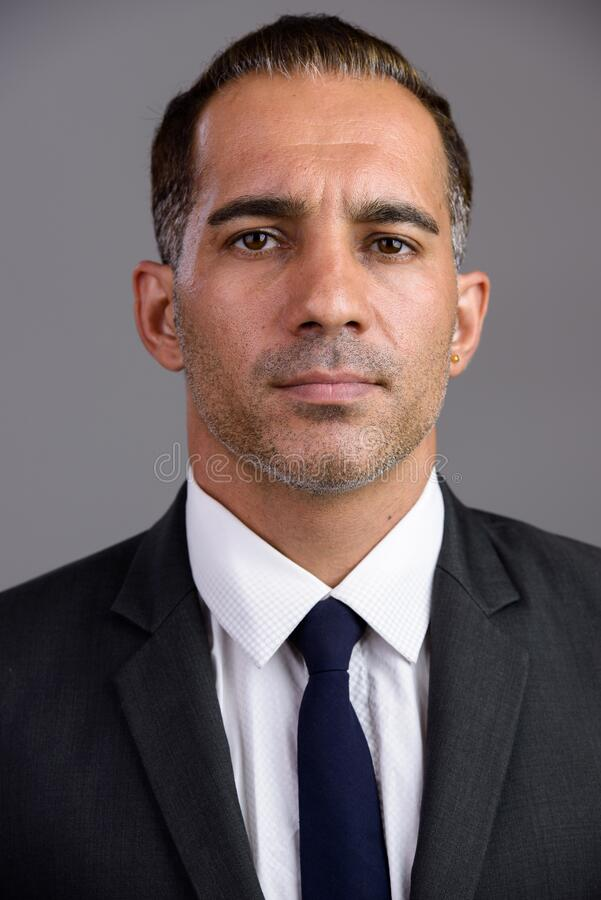 Face of mature handsome Persian businessman in suit stock images