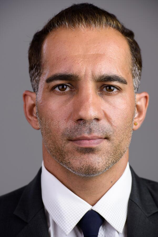Face of mature handsome Persian businessman in suit stock image