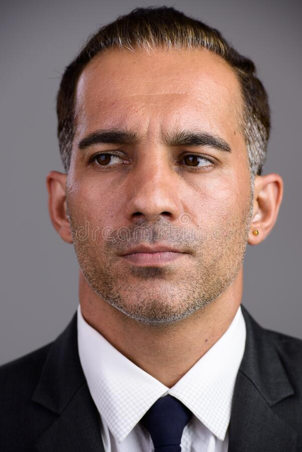 Face of mature handsome Persian businessman in suit thinking royalty free stock photos