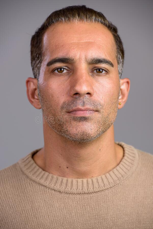 Face of mature handsome Persian man looking at camera stock photo
