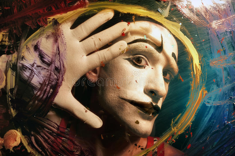 Face of Mime behind glass with multi-colored paint stains royalty free stock photography