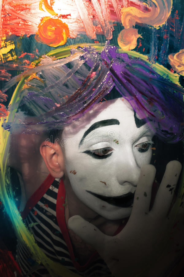 Face of Mime behind glass with multi-colored paint stains royalty free stock photo