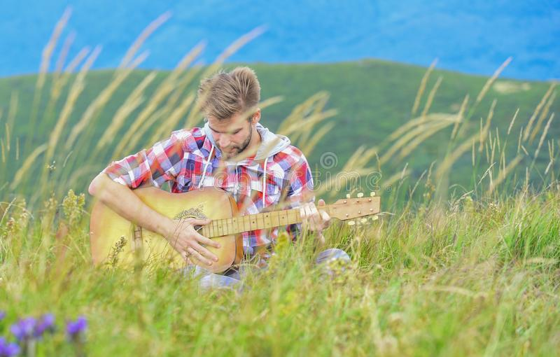Face the music. acoustic guitar player. country music song. sexy man with guitar in checkered shirt. hipster fashion. Western camping and hiking. happy and royalty free stock images
