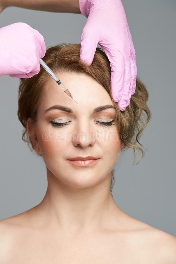Face needle injection. Young woman cosmetology procedure. Doctor gloves royalty free stock photo