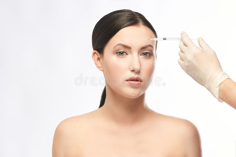 Face needle injection. Young woman cosmetology procedure. Doctor gloves royalty free stock photography