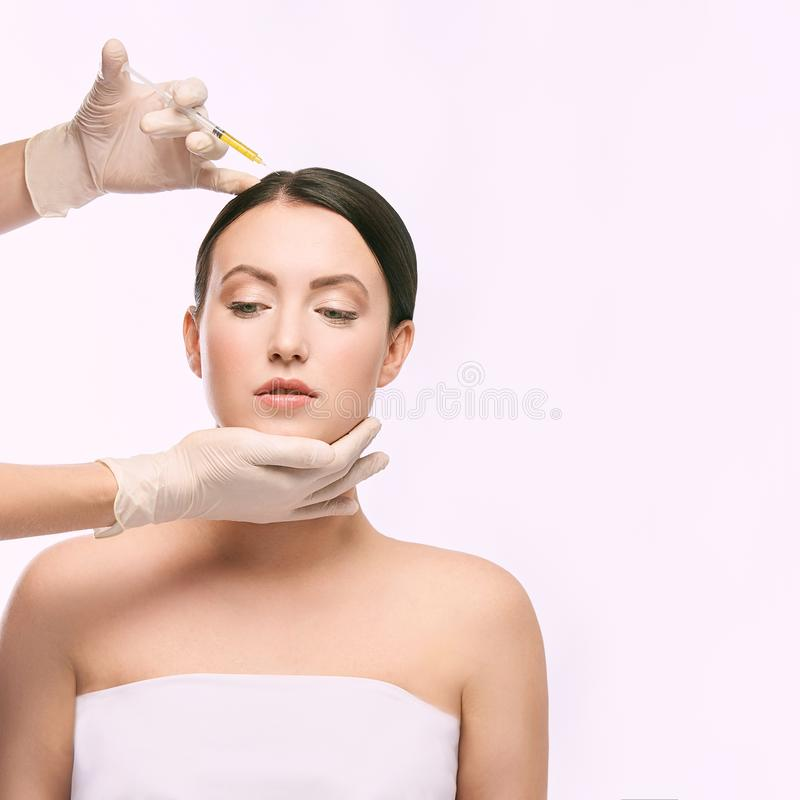 Face needle injection. Young woman cosmetology procedure. Doctor gloves stock images
