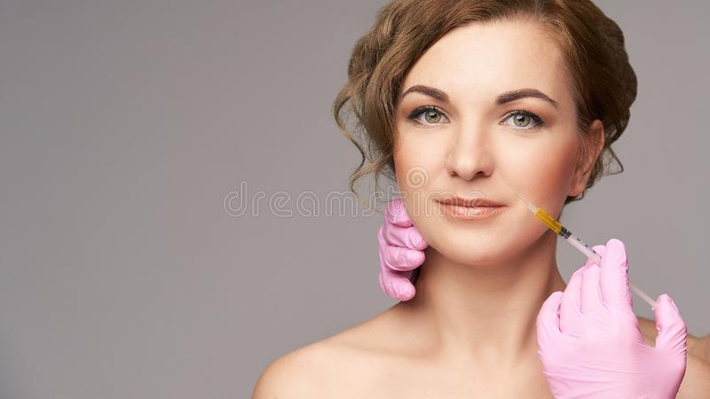 Face needle injection. Young woman cosmetology procedure. Doctor gloves. Lips stock photos