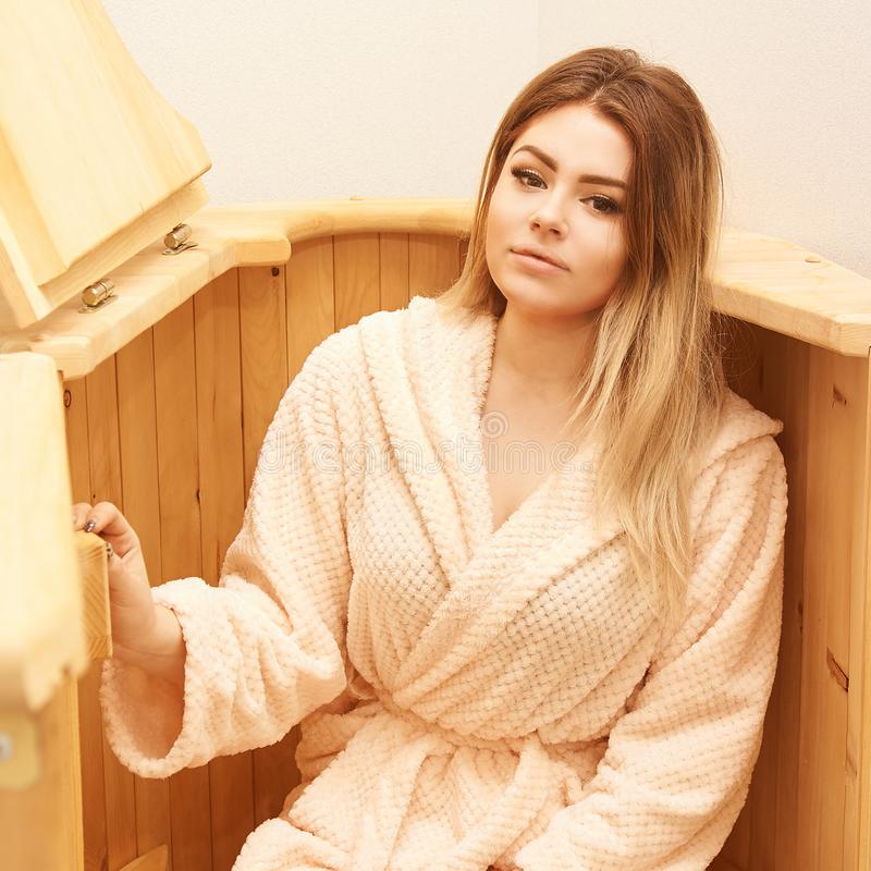Barrel cedar. Wellness spa sauna. Aromatherapy treatment. Young beauty woman. Girl face royalty free stock photography