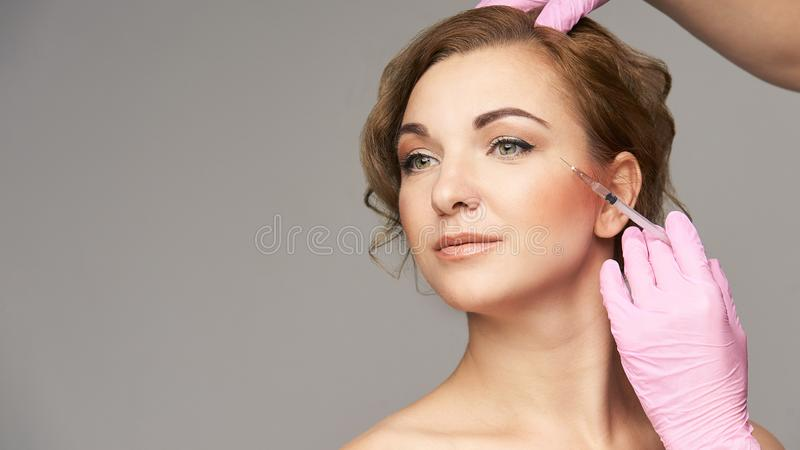 Face needle injection. Young woman cosmetology procedure. Doctor gloves. Wrinkles royalty free stock image