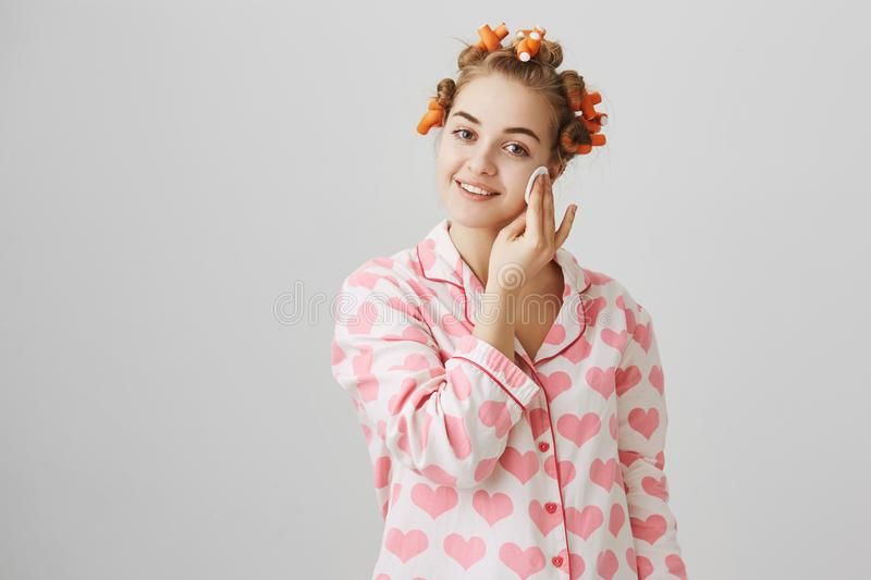 Face needs proper treatment. Good-looking cute european girlfriend in nightwear and hair curlers wiping skin with cotton royalty free stock image