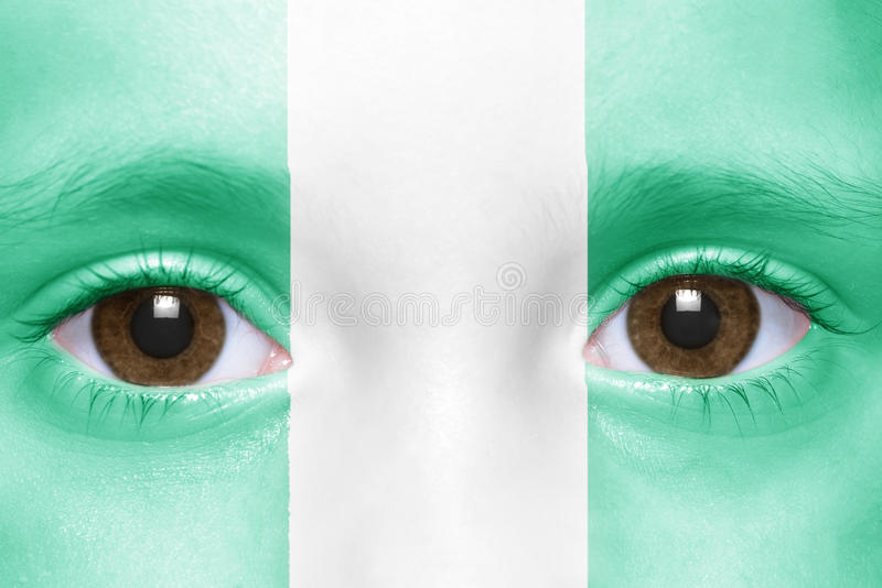 Face with nigerian flag. Human`s face with nigerian flag royalty free stock photography