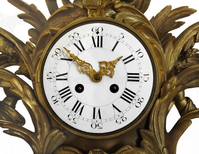 Face of a old fancy clock isolated. Close-up of the face of a fancy antique clock, in a gilt gold setting. Isolated on white royalty free stock photography