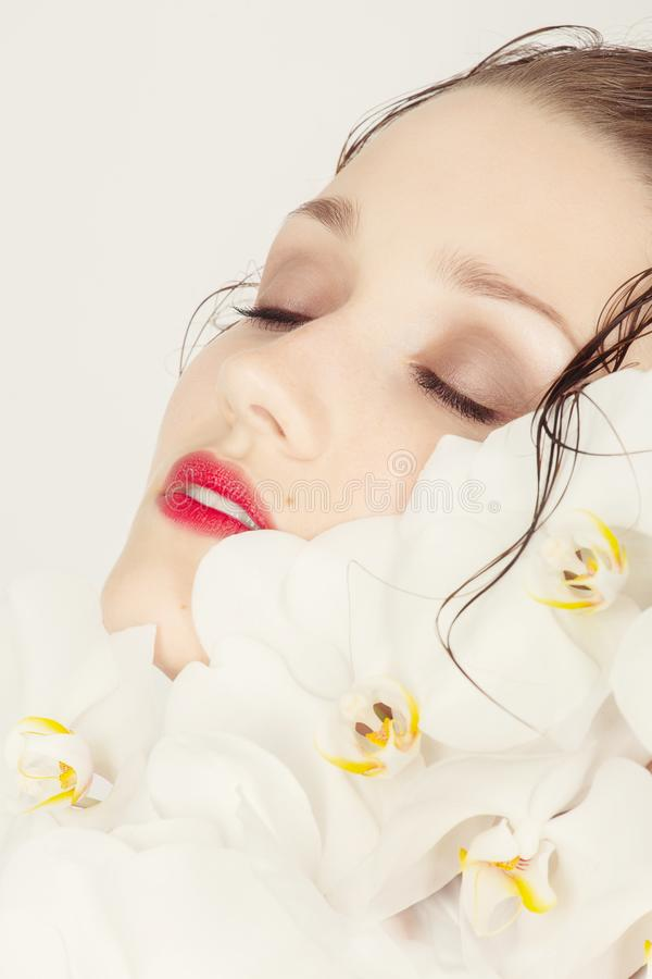 Face with orchids. Beautiful female face with luxury makeup on white orchids, closed eyes, wet hair royalty free stock image