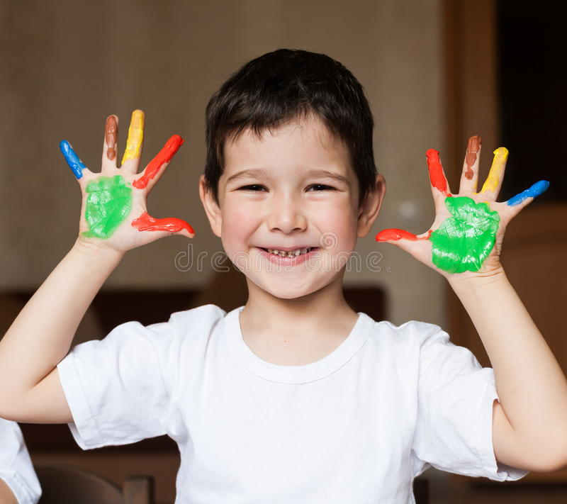 Face, painted, hands, white t-shirt. Beautiful little brunet hair boy, has happy fun smiling face, brown eyes, white t-shirt. Painted in skin hands. Child stock photo