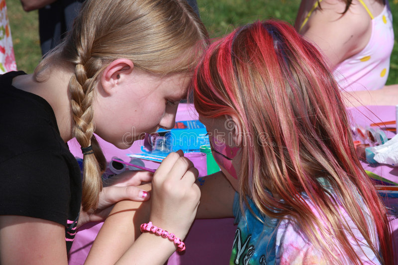Face painting. 13 year old girl painting a younger childs face at a birthday party royalty free stock photo