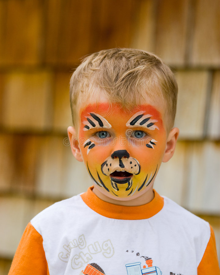 Face painting. Boy gets face painted like tiger