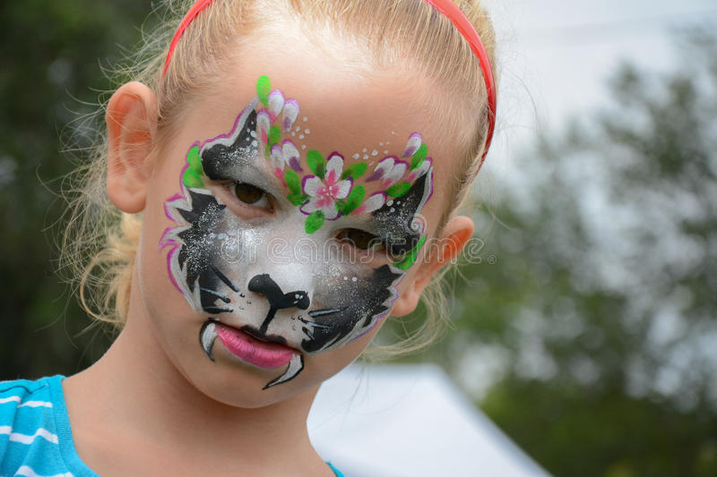 Face painting. Beautiful girl with face painting of black cat poses in the park royalty free stock image