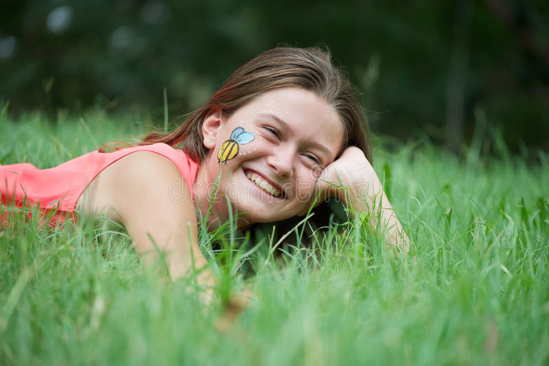 Face Painting. Cute girl lying in the green grass. She has a big smile and wears a honeybee face painting on her cheek royalty free stock photography