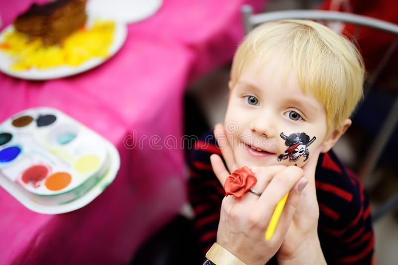 Face painting for cute little boy during kids birthday party. Face painting for cute little boy during kids merriment. Face paint for `Pirates` theme on birthday royalty free stock photo