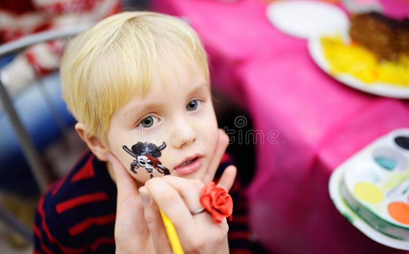 Face painting for cute little boy during kids birthday party stock photos