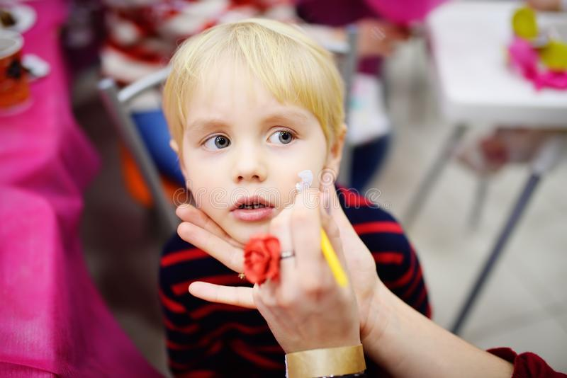 Face painting for cute little boy during kids birthday party stock photography