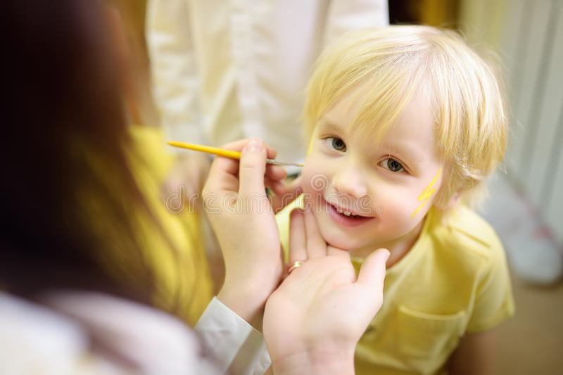 Face painting for cute little boy during kids merriment. Face paint for `Thunderbolt ` theme on birthday party. Preschooler kids celebrating party in royalty free stock photo