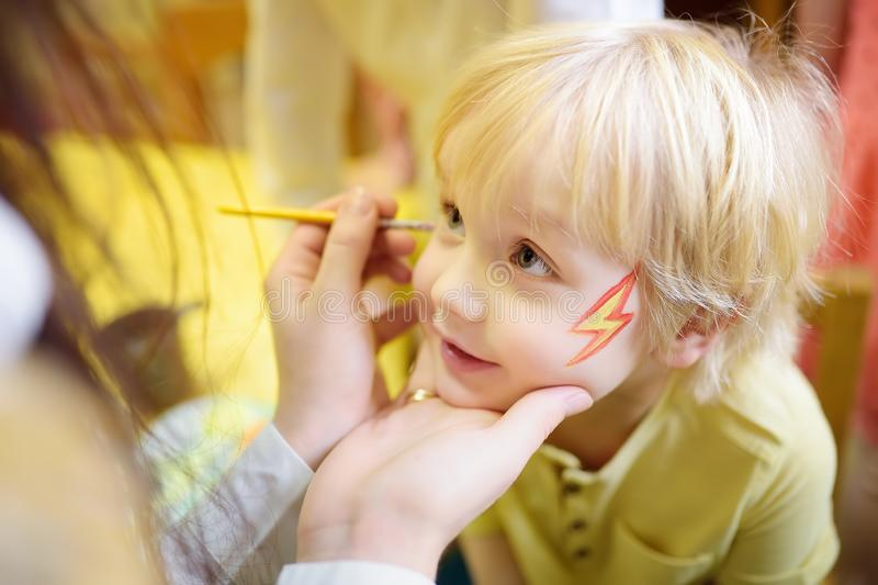 Face painting for cute little boy during kids merriment. Face paint for `Thunderbolt ` theme on birthday party. Preschooler kids celebrating party in stock images